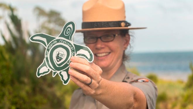 A National Park Service ranger holds a turtle magnet to remind visitors it's the time of year to turn off outdoor lights at night to protect nesting turtle habitats.