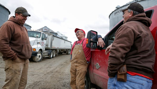 In this Tuesday, April 4, 2017, photo, Blake Hurst, a corn and soybean farmer and president of the Missouri Farm Bureau, center, jokes with his brothers Brooks Hurst, left, and Kevin Hurst, right, on his farm in Westboro, Mo. U.S. President Donald Trump has vowed to redo the North American Free Trade Agreement, but NAFTA has widened access to Mexican and Canadian markets, boosting U.S. farm exports and benefiting many farmers. Many farmers worry that Trump's policies will jeopardize their exports just as they face weaker crop and livestock prices.