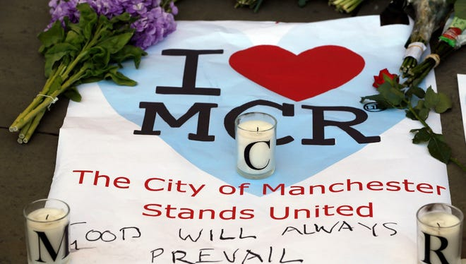 A sign is seen with flowers and candles after a vigil in Albert Square in Manchester, England, on Tuesday, the day after the suicide attack at an Ariana Grande concert that left 22 people dead and scores injured.