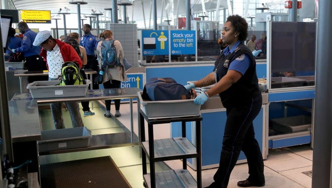 A Transportation Security Administration officer handles a bag for secondary screening at a new checkpoint with automated screening lanes at Terminal 4 at John F. Kennedy International Airport  in Queens, New York, on May 17, 2017.