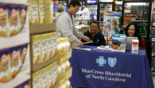 In this Saturday, Nov. 22, 2014, file photo, Blue Bridge Benefits LLC agent Patricia Sarabia, right, and Adolfo Briceno, left, with Spanish Speaking LLC, help a potential customer with Blue Cross Blue Shield at a kiosk promoting health insurance under the federal Affordable Care Act, at Compare Foods in Winston-Salem, N.C. People shopping for insurance through the Affordable Care Act in yet more regions will be facing higher prices and fewer choices in the coming year as insurance companies lay out their early plans for 2018. Blue Cross and Blue Shield of North Carolina said Thursday, May 25, 2017, it wants a 23 percent price hike in 2018 because it doesn't expect crucial payments from the federal government to continue.