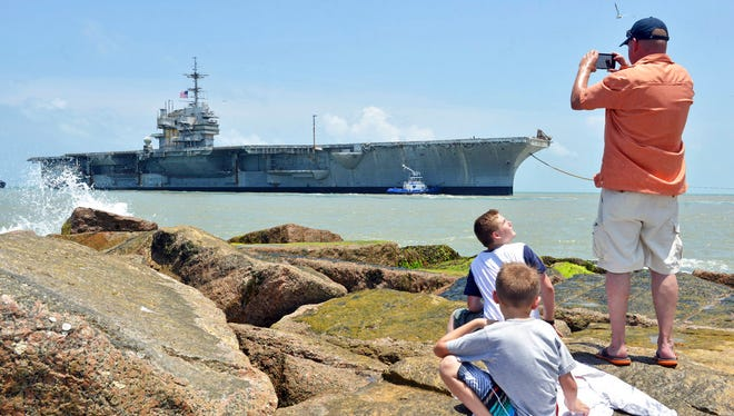 United States Veteran Philip Stringfellow who served during the Gulf War looks for one last time with his children along the Isla Blanca Park jetties on South Padre Island as former USS Independence aircraft carrier enters the jetties to its final destination to be scrapped at International Shipbreaking Ltd., Thursday, June 1, 2017. (Miguel Roberts/The Brownsville Herald via AP)