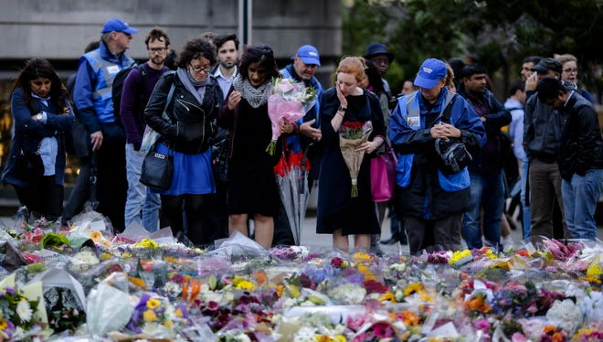 People look at floral tributes on London Bridge in London, Tuesday, June 6, 2017.
