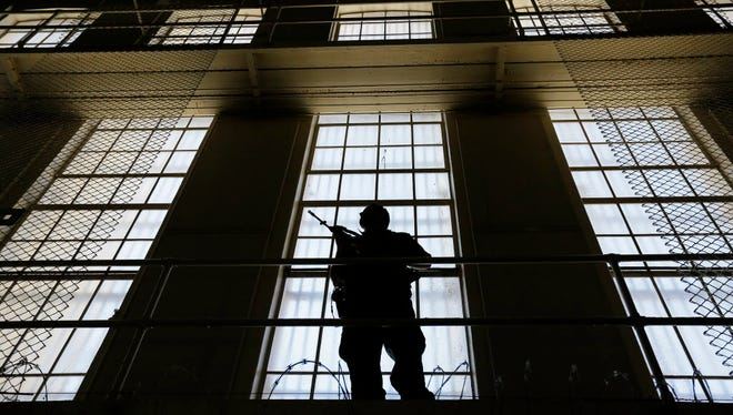 A guard stands watch over the east block of death row at San Quentin State Prison in San Quentin, Calif.