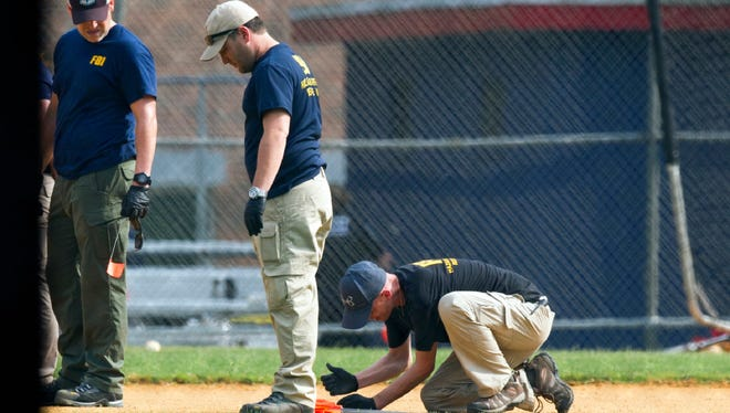 A FBI Evidence Response Team marks evidence on the ball field which is the scene of a multiple shooting in Alexandria, Va., Wednesday.