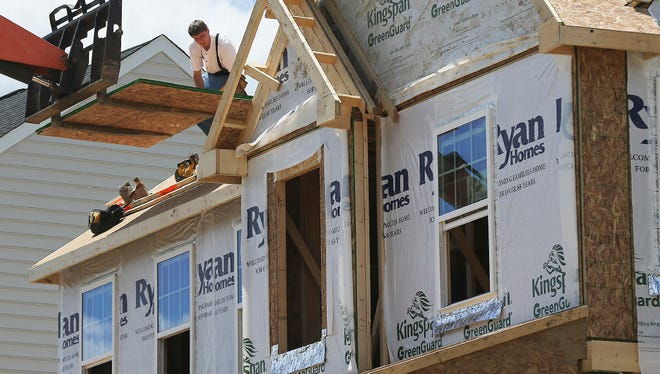In this Thursday, June 1, 2017, photo, builders work on the roof of a home under construction at a housing plan in Jackson Township, Butler County, Pa. On Friday, June 16, 2017, the Commerce Department reports on U.S. home construction in May.