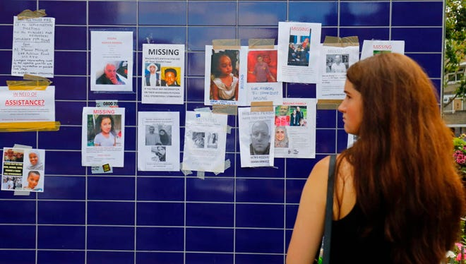 A woman looks at posters of missing people stuck to a wall, the victims of the June 14 Grenfell Tower block fire, in Kensington, west London, on June 17, 2017.