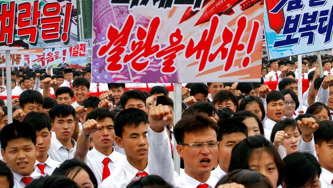 "Tens of thousands of men and women pump their fists in the air and chant as they carry placards with anti-American propaganda slogans at Pyongyang's central Kim Il Sung Square on Sunday, June 25, 2017 to mark what North Korea calls ""the day of struggle against U.S. imperialism"" – the anniversary of the start of the Korean War."