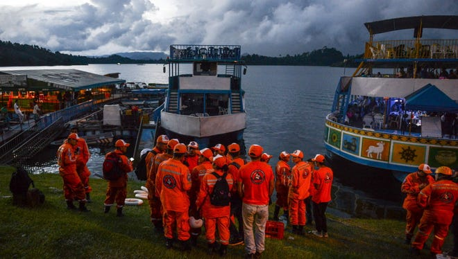 Rescue officials gather to take part in a search for survivors after the tourist boat Almirante sank in the Reservoir of Penol in Guatape municipality in Antioquia June 25, 2017.