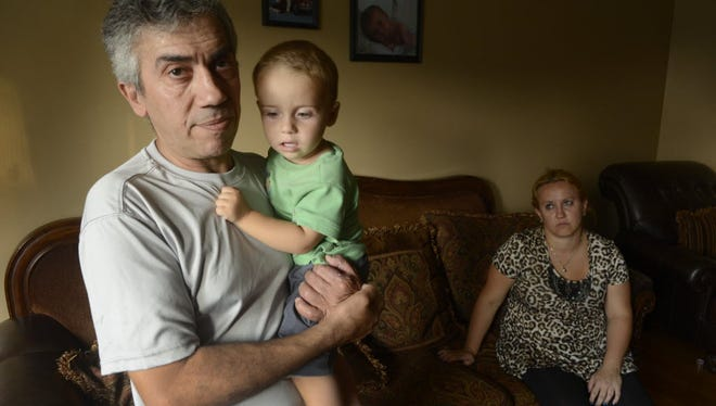 Jamal Laham with his 1½-year-old son, Ayden, and wife, Mirlinda Kurtisi, at their home in Garfield. After a 2017 chemical attack, Laham pored over the heartbreaking images of lifeless children in Damascus, Syria, hoping he wouldn't see his loved ones among them.