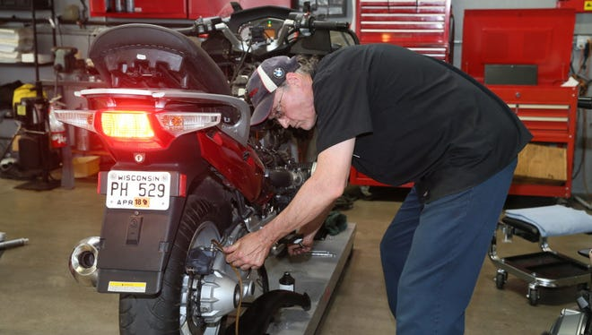 Mike Polek, a service technician Schlossmann Motorcycles of Milwaukee, does a power brake flush on a BMW R12RT motorcycle Wednesday.