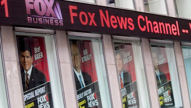 Posters featuring Fox News talent including one of Bill O'Reilly, second from right, are displayed on the News Corp. headquarters building in Midtown Manhattan. Bill O'Reilly lost his job at Fox News Channel following reports that five women had been paid millions of dollars to keep quiet about harassment allegations.