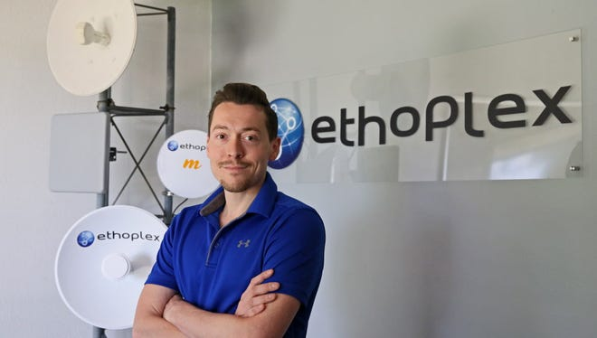 Keefe John, CEO of Ethoplex, stands in his office with some of the antennas the company uses to provide clients high-speed internet.