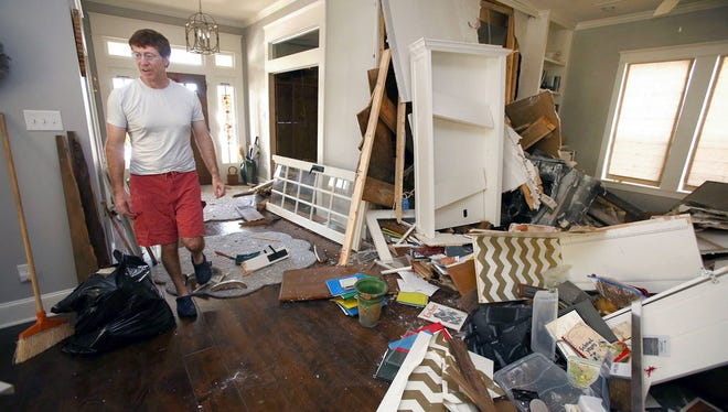 """Ken Downs surveys the damage to his home, Saturday, July 8, 2017, after a car drove through the home. Police said a man suspected of drunken driving smashed his car through the front of a """"Fixer Upper"""" home in North Waco early Saturday morning, capping more than a year of frustration for its owners, who feel their complaints about neighborhood crime have gone unheard. (Jerry Larson/Waco Tribune Herald via AP)"""