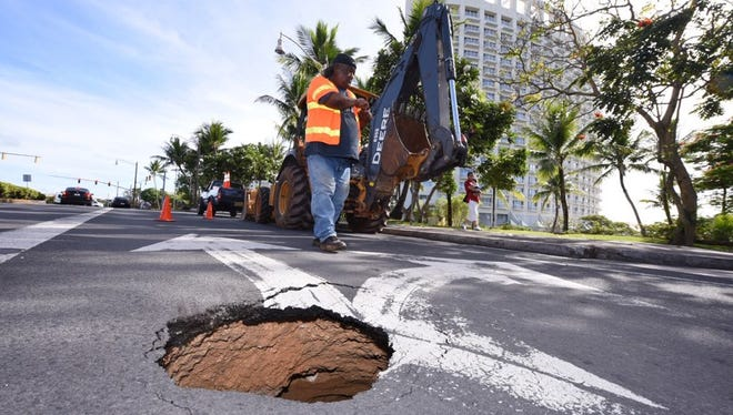 A worker from the Department of Public Works is on the scene of a sinkhole on San Vitores Road July 12, 2017.