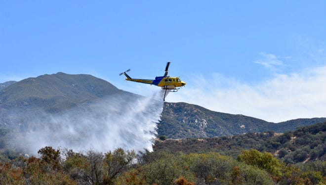 A Ventura County Fire Department helicopter drops water on a small brush fire in the Upper Ojai Valley Thursday morning.