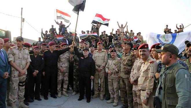 Iraq's Prime Minister Haider Abadi raises the national flag in Mosul Iraq, on July 10, 2017.
