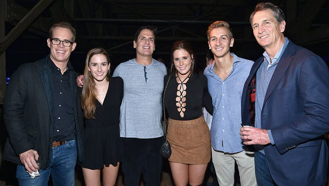 AXS TV Chairman, CEO and President Mark Cuban (3rd L) poses with (from L) TV/radio personality Joe Buck, Trudy Buck, Natalie Buck, Jac Collinsworth and TV personality/retired NFL player Cris Collinsworth at the DirecTV Super Saturday Night co-hosted by Mark Cuban's AXS TV at Pier 70 on February 6, 2016 in San Francisco, California.
