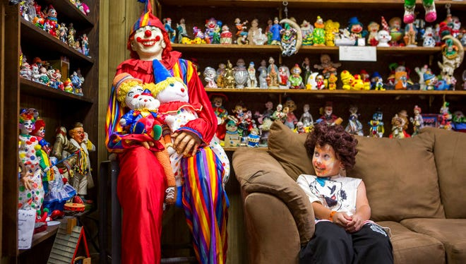 "Kai James, 9, glances over at the life-size clown known as ""Mr. Creepy"" in the lobby of the Clown Motel in Tonopah on Tuesday, July 25, 2017. James came with his brother and mother from Las Vegas to stay for a night and dressed up in clown attire."