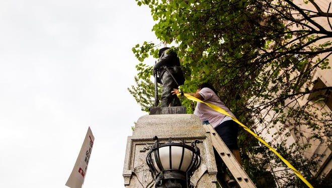 An unidentified protester climbs a ladder to place a rope around a Confederate statue during a rally Monday, Aug. 14, 2017, in Durham, N.C. Protesters toppled the nearly century-old statue of a Confederate soldier Monday at the rally against racism. The Durham protest was in response to a white nationalist rally held in Charlottesville, Va., over the weekend. (Casey Toth/The Herald-Sun via AP)