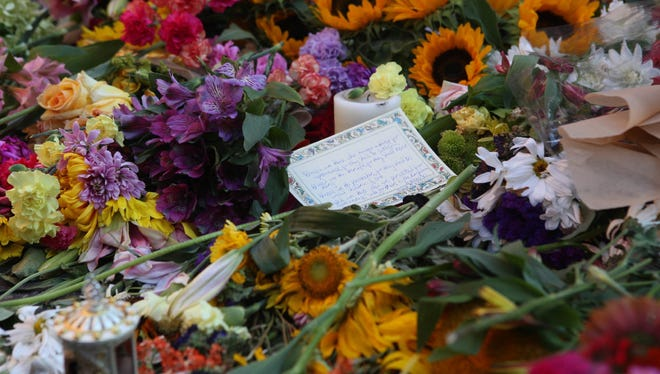 A note written to Heather Heyer sits among flowers at a memorial in Charlottesville, Va.