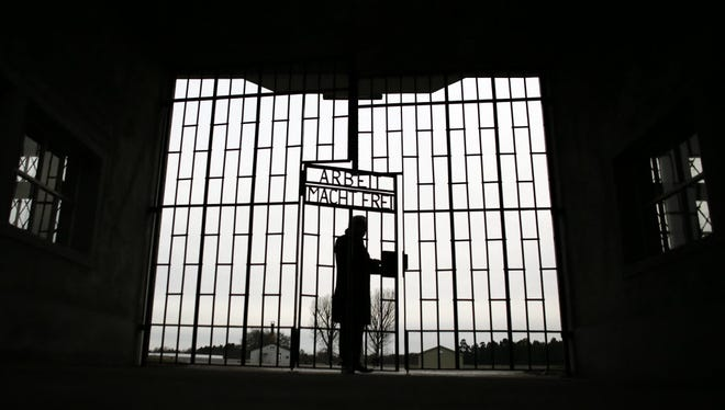 A man enters the Sachsenhausen Nazi death camp through the gate with the phrase 'Arbeit macht frei' (work sets you free) in Oranienburg, about 18 miles north of Berlin.