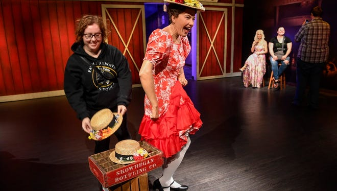 Danielle Rossman of Nashville replaces one of Minnie Pearl's hats after posing with her wax figure this month at the Madame Tussauds at the Opry Mills Mall.