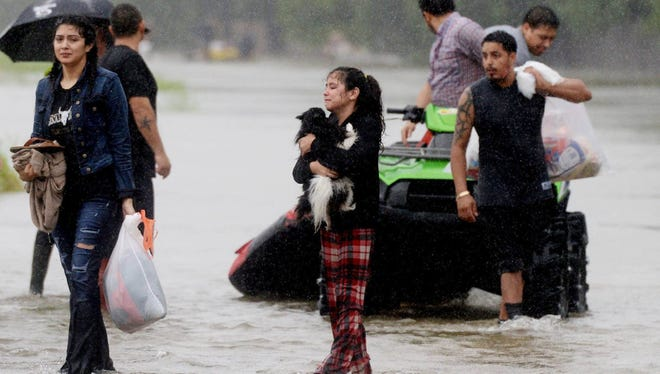 Residents are rescued Monday from floodwaters caused by Hurricane Harvey.