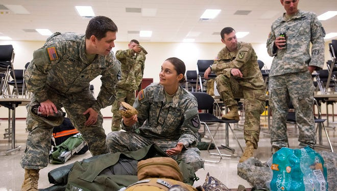 Spc. Garth Parks, left, and Pfc. Taylor Garen, center, chat as Garen packs her alert bag at the Tyler Armed Forces Reserve Center in Tyler, Texas, on Monday, Aug. 28, 2017. Unit 136 military police battalion has deployed some members and equipment for Hurricane Harvey relief efforts in Houston while the headquarters unit waits for their mission instructions. (Chelsea Purgahn/Tyler Morning Telegraph via AP)