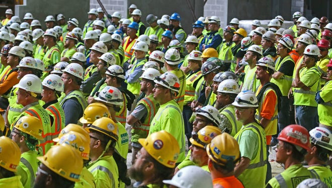"""Milwaukee's building boom has created many jobs in the construction industry. Workers at the Milwaukee Bucks arena project are shown here at the Aug. 24  """"topping off"""" ceremony as the final beam in the roof was raised into place."""