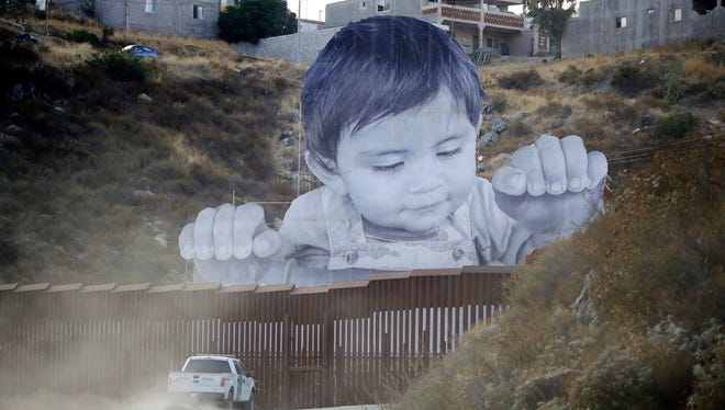 A Border Patrol vehicle drives in front of an art installation in Tecate, Mexico, just beyond the border fence. A French artist known as JR hopes it will prompt discussion about immigration. The installation will be there for about a month.