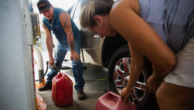 Lonnie Stuber, left, and Sharon Holley fill gas tanks at the City Gate Shell station on White Lake Boulevard, just off of Collier Boulevard north of I-75, on Tuesday, Sept. 12, 2017, two days after Hurricane Irma. After waiting for an hour, the two filled gas tanks for their neighbors who have generators at home, but no way of getting to a gas station.