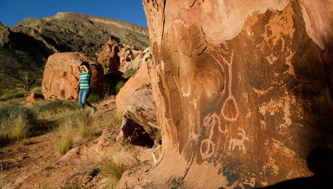In this May 26, 2017, photo, Susie Gelbart walks near petroglyphs at the Gold Butte National Monument near Bunkerville, Nev. Interior Secretary Ryan Zinke is recommending that six of 27 national monuments under review by the Trump administration be reduced in size, along with management changes to several other sites.