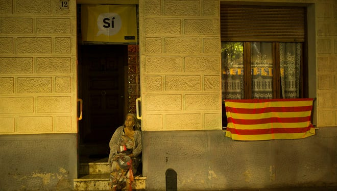 A woman sits outside her house as she hits pots to make noise encouraging Catalans to vote for 'Yes' in the region's Oct. 1 referendum on independence from Spain. The vote could be blocked by Madrid. (Photo: Cornella, on the outskirts Barcelona,  Sept. 28.)