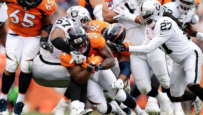Oct 1, 2017; Denver, CO, USA; Denver Broncos running back C.J. Anderson (22) is tackled by Oakland Raiders linebacker Cory James (57) and free safety Reggie Nelson (27) as offensive guard Max Garcia (76) and offensive guard Ronald Leary (65) block in the third quarter at Sports Authority Field at Mile High. Mandatory Credit: Isaiah J. Downing-USA TODAY Sports