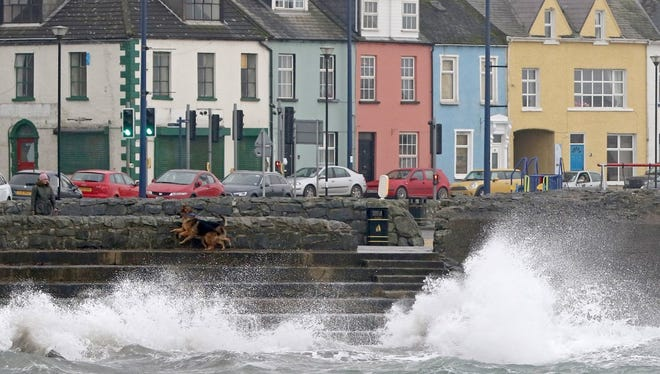 A woman walks her dogs beside the stormy sea in the coastal village of Donaghadee on the Irish Sea coast, east of Belfast in Northern Ireland, as the region braces for the passing of Ophelia.