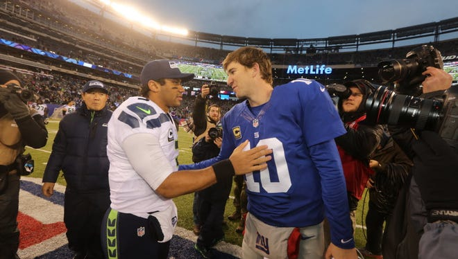 Seattle Seahawks quarterback Russell Wilson and New York Giants quarterback Eli Manning meet up at midfield following their December 15, 2013 game against one another at MetLife Stadium in East Rutherford, NJ. The Seahawks and Giants meet there again this Sunday.