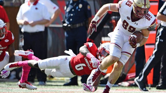 Boston College Eagles tight end Tommy Sweeney (89) avoids the tackle of Louisville Cardinals cornerback Russ Yeast (6) during the second second half at Papa John's Cardinal Stadium. Boston College defeated Louisville 45-42.