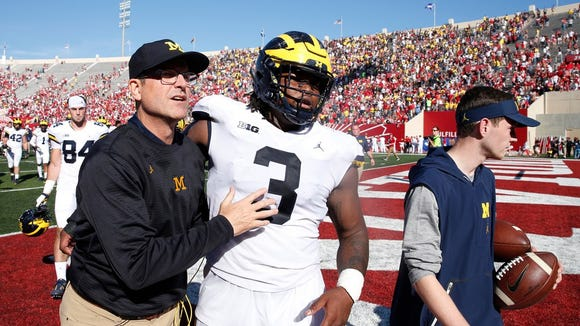 Michigan Wolverines coach Jim Harbaugh walks off the field with defensive lineman Rashan Gary (3) after the game against the Indiana Hoosiers at Memorial Stadium. Michigan defeats Indiana 27-20 in overtime.