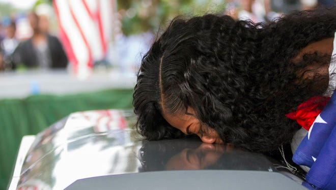 "Myeshia Johnson kisses the casket of her husband, Sgt. La David Johnson during his burial service at Fred Hunter's Hollywood Memorial Gardens in Hollywood, Fla. Myeshia Johnson told ABC's ""Good Morning America"" on Monday, Oct. 23, 2017, that she has nothing to say to the president, adding that his phone call to her made ""me cry even worse."""