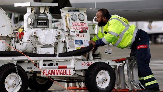 An  airport worker adjusts equipment used to pump fuel into airplanes on Dec. 16, 2015, at Seattle-Tacoma International Airport in Seattle, Wash.
