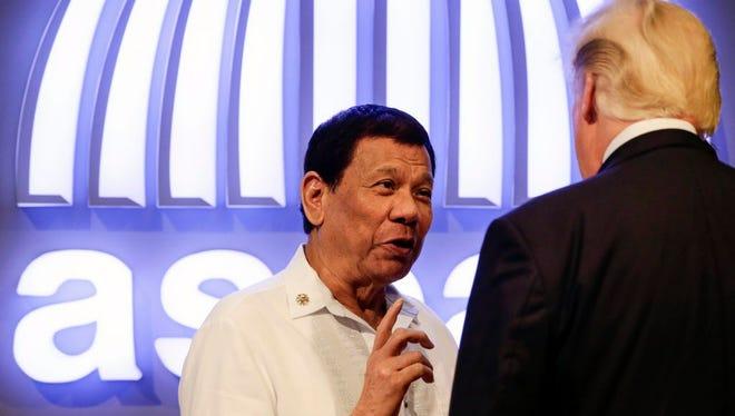 Philippine President Rodrigo Duterte gestures to President Trump before the opening ceremony of the 31st ASEAN Summit in Manila Nov. 13, 2017.