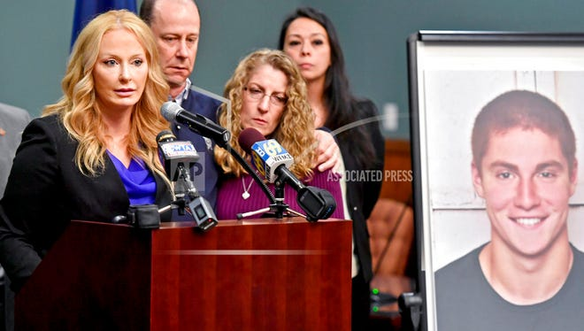 In this May 5, 2017, file photo, Centre County, Pa., District Attorney Stacy Parks Miller, left, announces findings an investigation into the death of Penn State University fraternity pledge Tim Piazza, seen in photo at right, as his parents, Jim and Evelyn Piazza, second and third from left, stand nearby during a news conference in Bellefonte, Pa. Parks Miller announced Monday, Nov. 13, 2017, that more charges have been filed against fraternity brothers after investigators recovered deleted surveillance video footage recorded before the Feb. 4, 2017, death of Piazza, of Lebanon, N.J., after a night of heavy drinking.