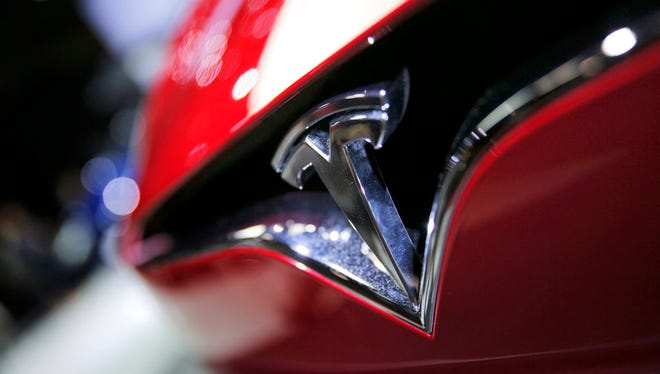 FILE - This Friday, Sept. 30, 2016, file photo shows the logo of the Tesla Model S on display at the Paris Auto Show in Paris.