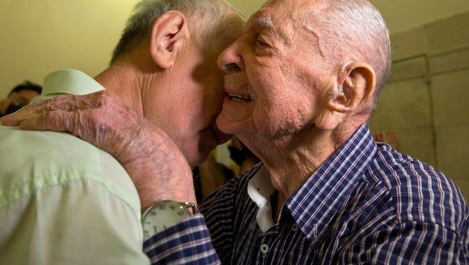 Israeli Holocaust survivor Eliahu Pietruszka, right, embraces Alexandre Pietruszka as they meet for the first time in Kfar Saba, Israel.