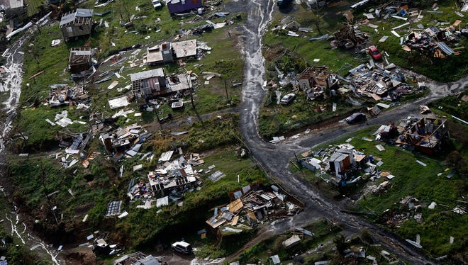 In this Sept. 28 photo, debris litters a destroyed community in the aftermath of Hurricane Maria in Toa Alta, Puerto Rico.
