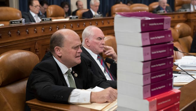 Seated behind a stack of IRS and tax volumes, Rep. Tom Reed, R-N.Y., left, joined by Rep. Mike Kelly, R-Pa., tax reform plan in the House of Representatives early in November.