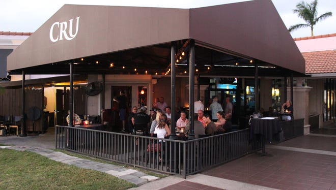 The outdoor bar at Cru has a casual cool vibe and is pet–friendly.