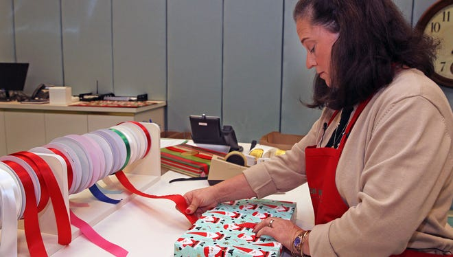 Caryn Lisowski, customer service manager at Von Maur at The Corners of Brookfield, takes pride in the department store's free gift wrapping for customers.