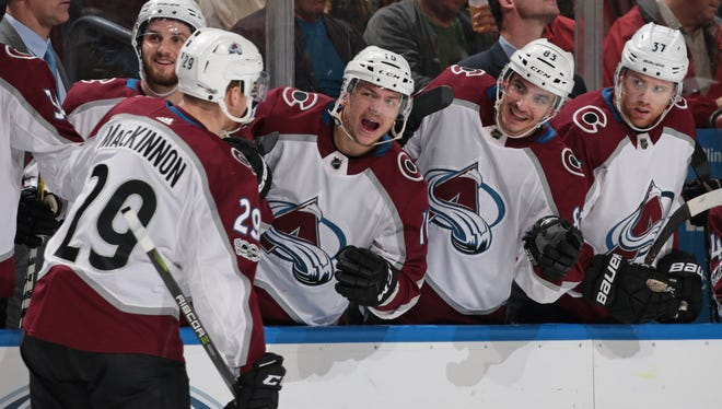Teammates congratulate Nathan MacKinnon after he scored a goal against the Florida Panthers.